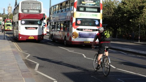Two double decker buses driving with a cyclist behind them