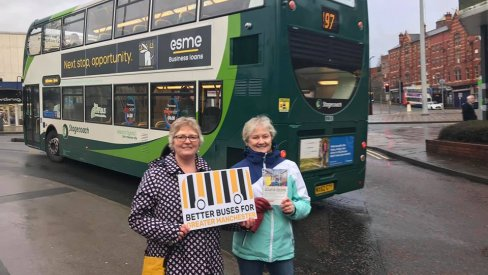 Two women hold a placard next to a bus saying 'Better buses for greater Manchester'