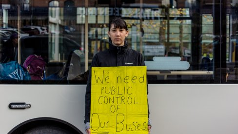 Woman holding a placard saying we need public control of our buses