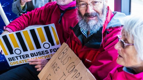 people sitting on a bus holding placards
